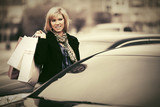 Young fashion woman with shopping bags next to car