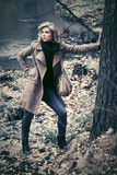 Young fashion blond woman with handbag walking in autumn forest