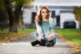 Sad young fashion woman with long curly hairs sitting on city street