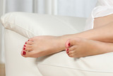 Woman feet with red pedicure on a couch