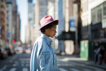 Young fashionable African American woman crossing the street