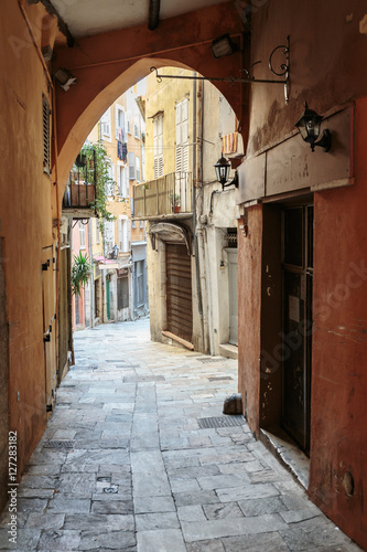 Narrow street with flowers in the old town in France © arbalest