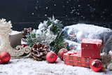Holidays background. Toys and presents on a dark wooden background with a lot of snow. Pine cones, presents, Christmas balls and other toys on a snow background. With falling snow.
