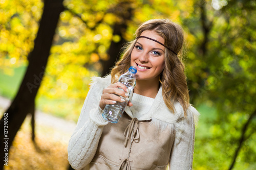 Poster Beautiful boho girl enjoys drinking water in the park.