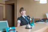 Friendly hotel worker posing behind reception