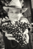 Young funny boy with bunch of grapes in hands, black and white