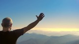 man standing on top of a mountain raising arms to the sky