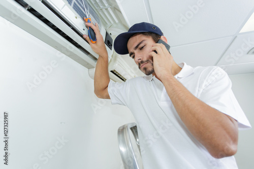 Poster young handyman repairing air conditioning system calling for help