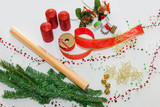 The decoration stage of DIY (do it yourself) making home decorative mantelpiece for Christmas holidays. Pine branches, red ribbon, candles, garland. Close up