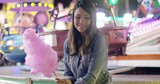 Happy young woman enjoying a night at a fairground or amusement park sitting holding a stick of colorful sticky candy floss
