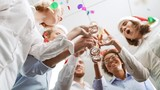 Cheerful colleagues rising their glasses for toast Office party Shot from below Slow motion