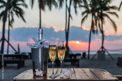 Plexiglas Zonsopgang New Year Celebration at beach/New Years Eve celebration background with pair of flutes and bottle of champagne in bucket.