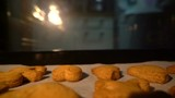 man pulls out ginger biscuits out of the oven