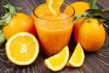 glass of fresh orange juice and oranges on wooden background - 127365972