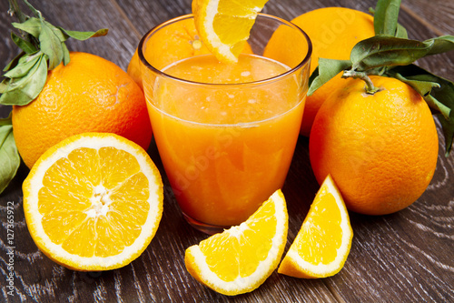 Poster Sap glass of fresh orange juice and oranges on wooden background