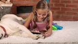Little girl playing on tablet computer laying with her labrador dog  - closeup, slide