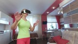 Young beautiful woman with virtual reality in modern interior first experience