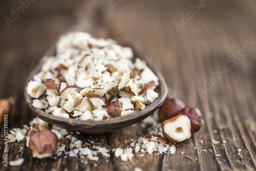 Foto Murales Wooden table with chopped Hazelnuts