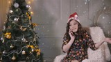 Young cute handsome girl speaks by mobile phone near the Christmas tree. Christmas celebration. HD.