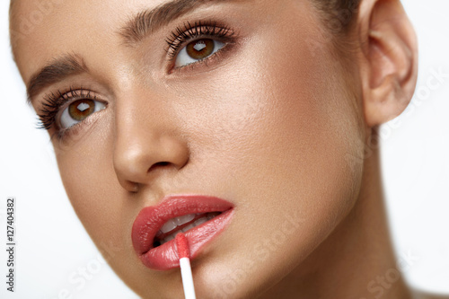 Tela Beautiful Woman Doing Makeup Using Lip Gloss On Lips. Cosmetics