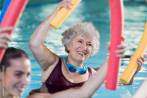 Leinwanddruck Bild Senior woman doing aqua aerobic