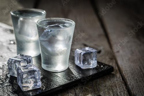 Foto Murales Vodka in shot glasses on rustic wood background