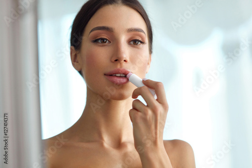 Beautiful Woman With Beauty Face Applies Balm On Lips. Skin Care Poster