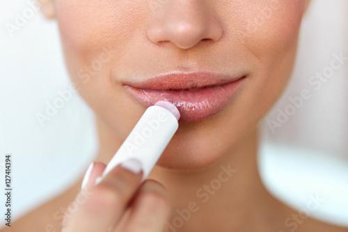 Beautiful Woman Applying Lip Protector On Lips Skin. Beauty Poster