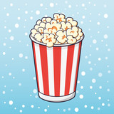 Popcorn in a red striped bucket on a snow background.