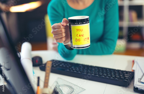 Poster Woman holding a cup of coffee with a motivational message: You can do it!
