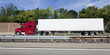 Red cab semi with white trailer on interstate under blue sky with trees in background. Horizontal.