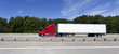 Red cab semi with white trailer on interstate under blue sky. Horizontal.