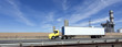 Yellow cab semi with white trailer on interstate under blue sky. Horizontal.