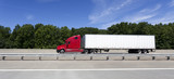 Red cab semi with white trailer on interstate under blue sky. Horizontal. - 127432558