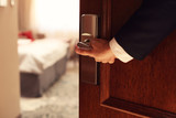 Hand of businessman opening hotel room - 127438985