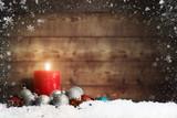 Weihnachtsschmuck und eine brennende Adventskerze mit Schneeflocken