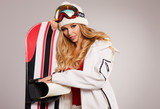 Sexy female in ski costume posing with snowboard in a studio