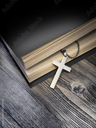 Poster Metal cross on top of a black book