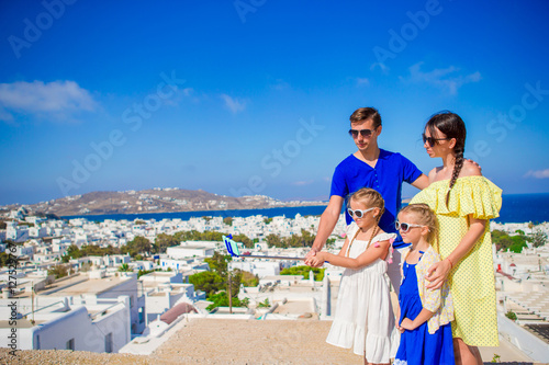 Family vacation in Europe. Parents and kids taking selfie background Mykonos town in Greece © travnikovstudio