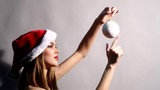Girl holding a white Christmas tree ball and spinning it