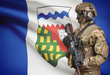 Soldier in helmet holding machine gun with Canadian province flag on background series - Northwest Territories