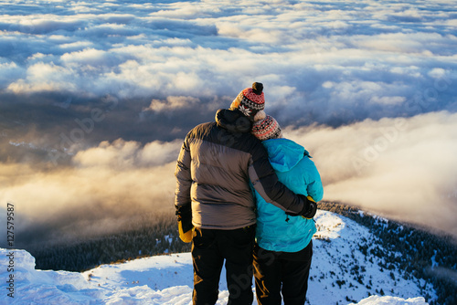 Loving couple stands on a top of the mountain and admire the inc