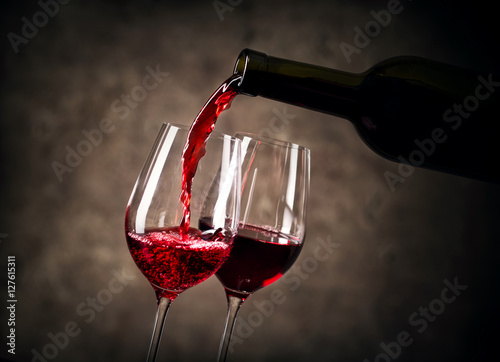 Fototapeta Red wine pouring into glass from bottle