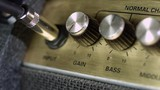 Close up of guitar amplifier panel with plugged guitar cable jack and adjusting knobs