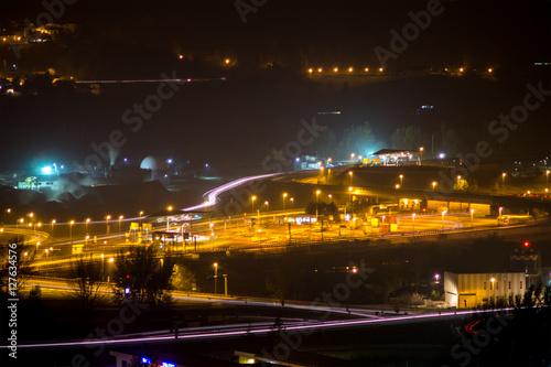 Foto op Aluminium Nacht snelweg city at night, with trails of the machines lights and smoke of factories. Time lapse di una citta di notte con scie di luci delle macchine e fumo delle fabbriche