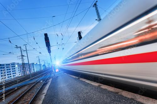 Nowożytny wysoki prędkość pociąg pasażerski na linii kolejowej w ruchu przy zmierzchem. Zatarcie pociągu podmiejskiego. Stacja kolejowa przy półmrokiem z rocznika tonowaniem. Tło podróży, turystyka kolejowa. Krajobraz przemysłowy. Pociąg