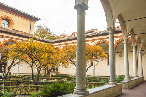 courtyard of church Santa Maria Delle Grazie, access to it's refectory hosting The Last Supper painting by Leonardo da Vinci with trees in autumn colors Poster