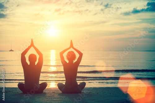 Fototapeta Silhouettes couple man and woman practicing yoga at sunset on the beach.