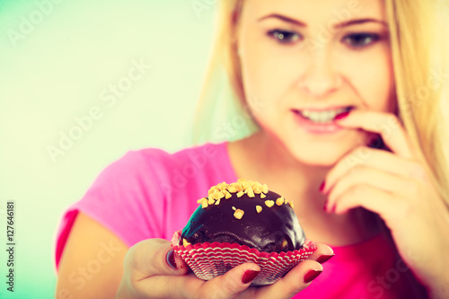 Poster Cute blonde woman thinking about eating cupcake