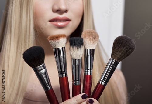 Póster beautiful young blond woman and brush for makeup